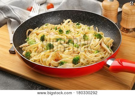 Frying pan with delicious chicken Alfredo on wooden board