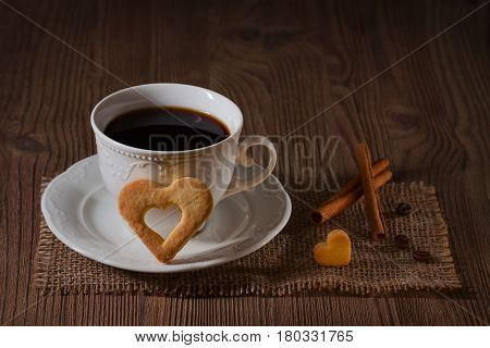 a cup of coffee and cookies like heart, cinnamon, coffee beans on wooden table on dark brown background