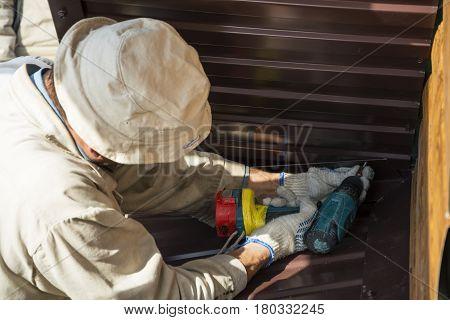 Man in gloves tightening screwdriver metal corner