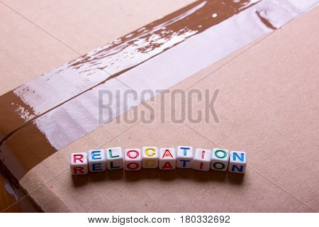 Moving to another office or house. Word relocation on a cardboard box with a sealed tape