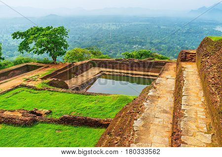 The cistern on Sigiriya rock summit is surrounded by ancient ruins of upper palace, Sri Lanka.