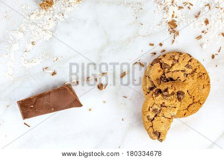 The process of making chocolate chips cookies. Overhead shot of biscuits with grated chocolate, flour, and copy space