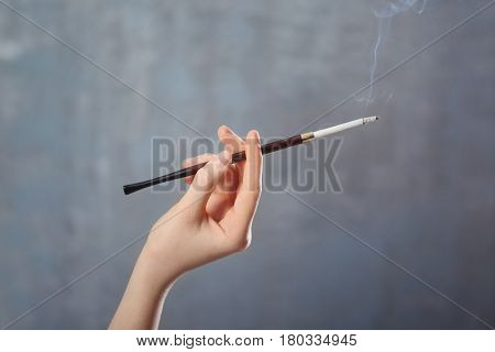 Female hand with cigarette holder on color background
