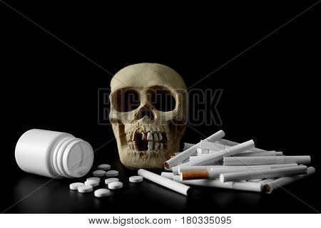 Skull, pile of cigarettes and pills on black background