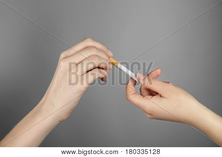 No smoking concept. Female hand taking offered cigarette on grey background