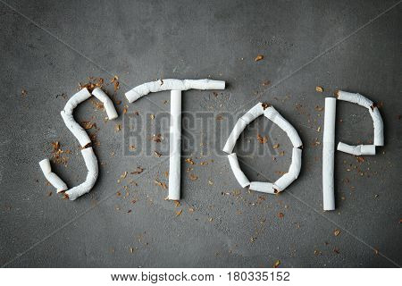Word STOP made of cigarettes on grey background