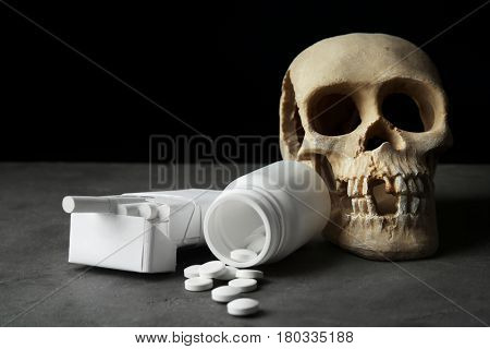 Skull, cigarettes and pills on grey table. No smoking concept