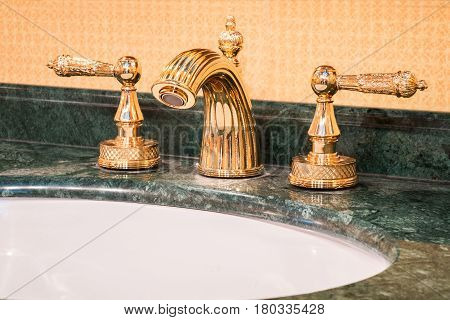 Retro mixer aucet in gold interior, bathroom
