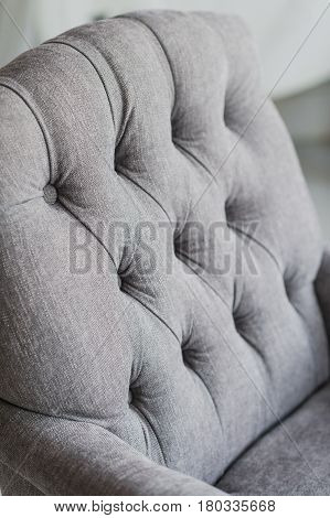 Seamless background texture close up of a grey sofa back with button detail on a thick cloth