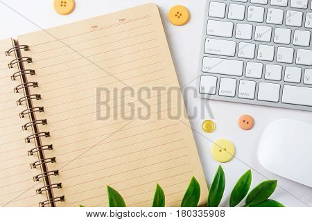 Open blank notebook with computer keyboard and mouse. Top view with copy space.