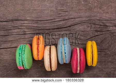 Cake macaron or macaroon colorful cookies. On an old wooden background. Empty space for text