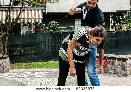 a guy helping a young girl with the heimlich desobstruction while she's choking