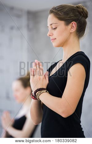 Two women in gym class, relaxation exercise or yoga class.