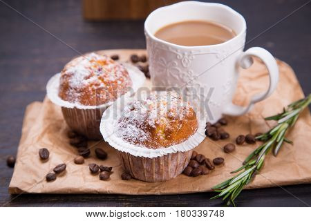 hot fresh coffee in white cup with muffin and rosemary