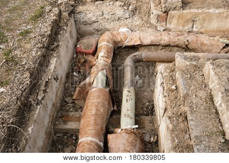 Old hot water pipes in open ditch overhead view