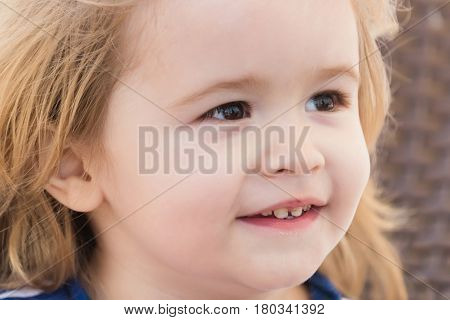 Happy cute baby boy small little child with adorable face brown eyes long blond hair smiling on sunny summer day outdoors on brown wicker background. childhood and happiness