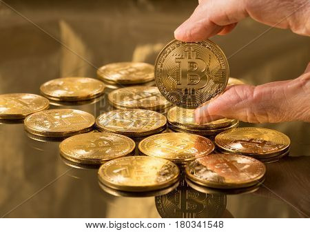 Stack of bit coins or bitcoin on gold background with a single coin held in hand to illustrate blockchain and cyber currency