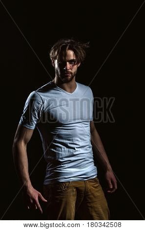 Handsome man or unshaven macho bodybuilder with stylish blond hair haircut in white tshirt with biceps triceps posing on black background