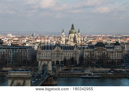 Scenic view of Pest side with St. Stephen's Basilica in center and Danube river with Chain Bridge in Budapest Hungary on a sunny day