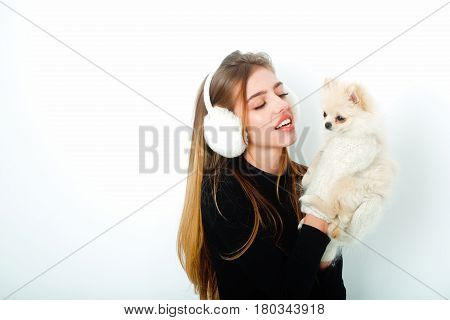Happy pretty girl or sexy woman with long hair in earmuffs black bodysuit woollen mittens winter fashion smiling to cute pomeranian dog or puppy pet in hands on white background copy space