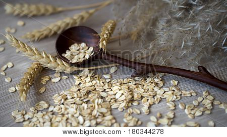 Close-up unprocessed oatmeal with wooden spoon and different spikes varieties against a plain coarse linen napkin.