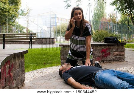 a girl helping a young guy after an heart attack with cardiopulmonary resuscitation