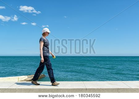 Young woman walking on the parapet of the sea promenade in the resort city of Alushta, Crimea, Russia