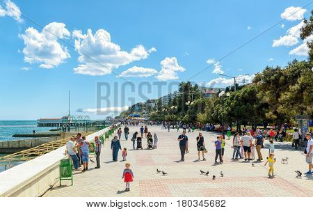 ALUSHTA, RUSSIA - MAY 15, 2016: Tourists walk along the promenade in the resort city of Alushta in Crimea.