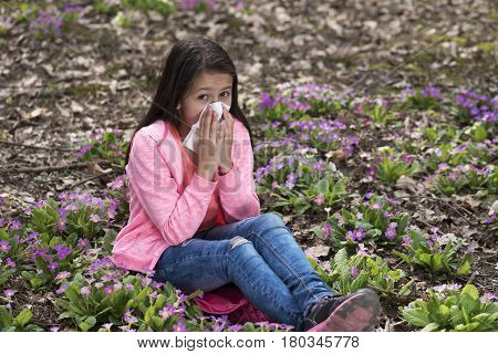 Girl blowing her nose because of allergic reaction