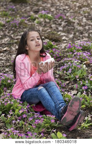 Girl in the wood sneezing because of the flowers