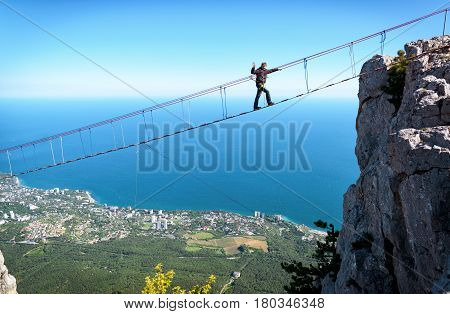 CRIMEA, RUSSIA - MAY 19, 2016: Tourist walking on rope bridge on the Mount Ai-Petri. Ai-Petri is one of the highest mountains in the Crimea and tourist attraction.