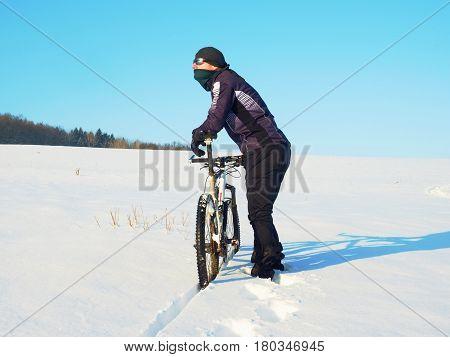 Biker Pushing Mountain Bike On Snow Drift. Freeze Sunny Winter Weather. Biker Is Pushing Bike In Dee