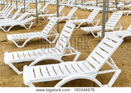 Beach chairs in the off-season. Empty sunbeds on a sandy beach.