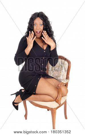 A closeup image of a very surprised African American woman with big eyes and open mouth kneeling in armchair isolated for white background.