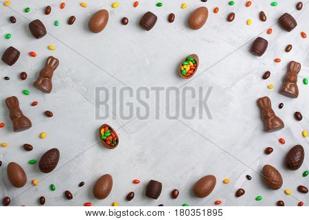 Chocolate easter eggs rabbits casks sweets and colored candies on concrete background. Horizontal orientation place for copyspace flatlay top view.