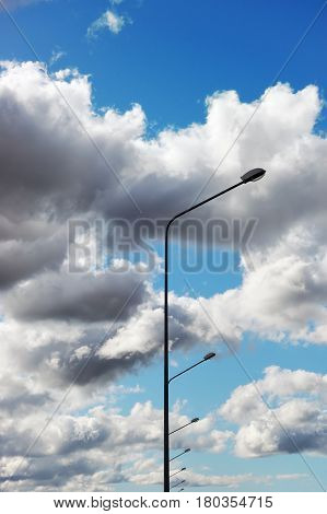 A row of street lamps against the dramatically overcast sky
