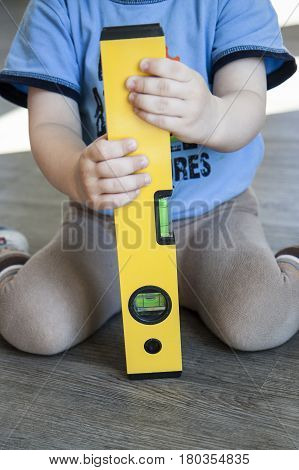 Spirit Level In Young Boy Hand - Child With Waterlevel