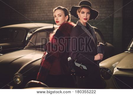 Two women among retro cars in garage