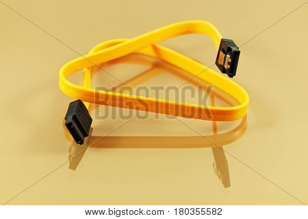 Yellow SATA cable on a reflective background