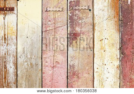 Fragment of a weathered multicoloured wooden fence texture