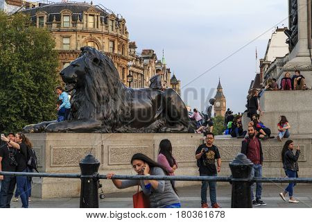 LONDON, GREAT BRITAIN - SEPTEMBER 7, 2014: Unidentified people rest on an autumn evening at the foot of Nelson's column in Trafalgar Square.