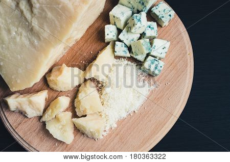 Grated Parmesan and sliced Blue cheese on wooden chopping board on dark background. Tasty appetizers. Top view.