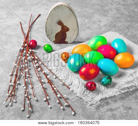 Easter Palm Sunday. Painted eggs of chicken and quail on cloth. Sprigs of the Easter willow. Wooden eggs with an Easter chicken. Gray concrete background.