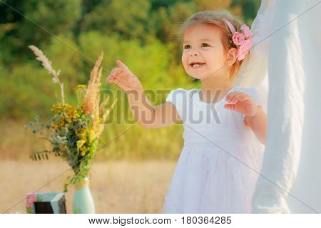 Little Girl Smiles And Shows Finger Upward.