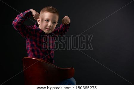 Close-up portrait of Cute young little angry boy in plaid shirt With a threat showing his strength with a confident pose isolated on black background. Human emotion facial expression.