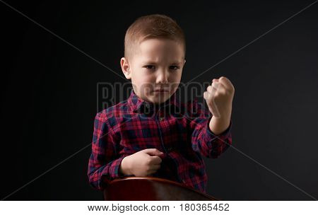 Close-up portrait of Cute young little angry boy in plaid shirt With a threat showing a fist isolated on black background. Human emotion facial expression.