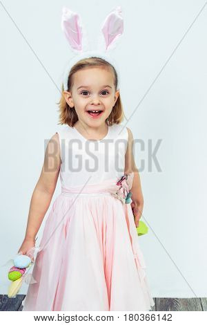 Happy preschool girl holding Easter egg decoration