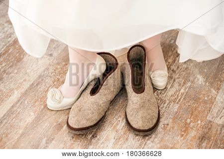 White wedding shoes on bride with felted slippers on the background of parquet floor