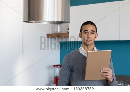 Serious Man With Tablet Looking At Camera