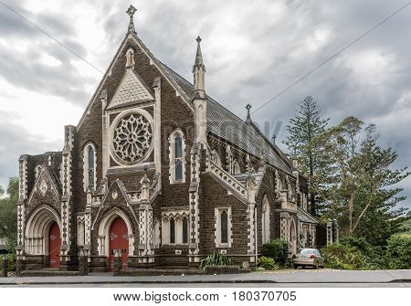 Auckland New Zealand - March 1 2017: Dark and white stone Saint Paul Church along Symonds Street under gray cloudy sky with green vegetation in back and a car on the side.